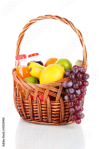 Foto op Canvas Sap Different fruits in wicker basket with juice isolated on white