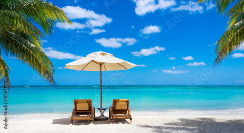 two deckchairs on the idyllic white beach turquoise sea