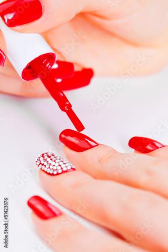 Obraz na płótnie Painting polish on fingers with red nails