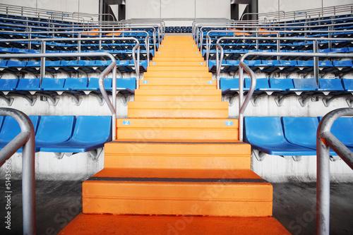 Plakat Pomarańczowy drabiny i niebieski trybuny na duży stadion piłkarski.