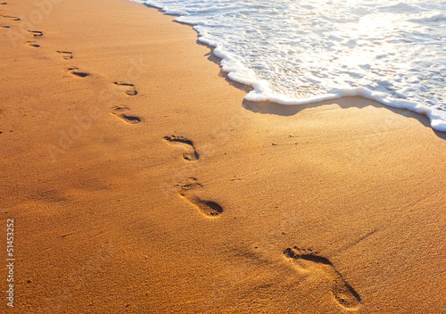 Staande foto Strand beach, wave and footsteps at sunset time