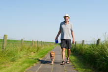Elderly Man Walking The Dog
