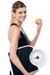 Fit girl holding fruit and weighing scale