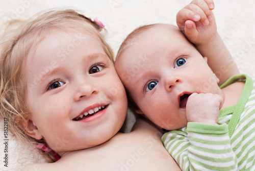 Photographie happy sister hugging baby brother