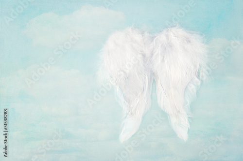 White angel wings on blue sky background