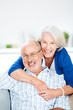 canvas print picture - glückliches älteres paar umarmt sich auf dem sofa