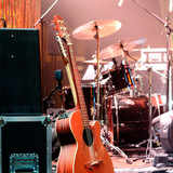 Acoustic guitar, drum kit, loudspeaker and other musical equipment on stage before concert. Red light. Concept image. Night club, performance, music band, singing, profession, art, instrument