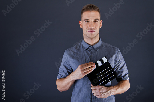 Fotografia  Man with movie clap over dark background