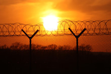 Security Fence At Sunset With ...