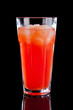 Red alcohol cocktail in highball glass isolated on black