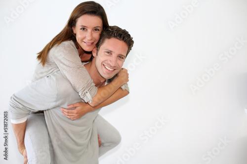 Stampa su Tela Handsome guy giving piggyback ride to girlfriend