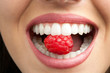 Leinwandbild Motiv Perfect teeth biting raspberry.