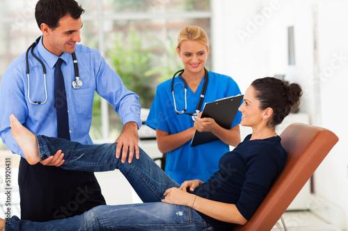 Fotografía  orthopaedist examining female patient's leg