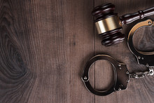 Handcuffs And Judge Gavel On Wooden Background