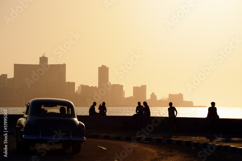 Old cars People and skyline of La Habana, Cuba, at sunset