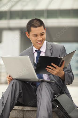 Fotografie, Obraz  Young businessman working outdoor