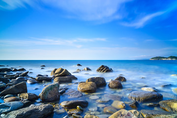Baratti bay, rocks in a blue ocean on sunset. Tuscany, Italy.