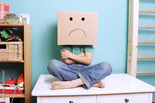Fényképezés  Trotziges Kind mit Karton auf dem Kopf