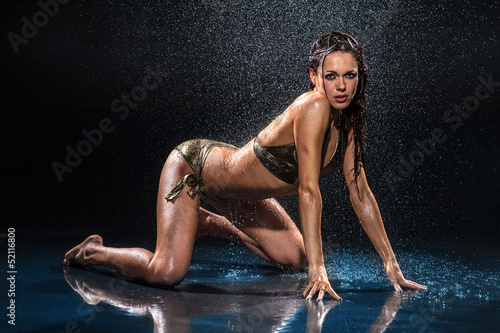 Sexy woman standing on her knees under rain. Studio photo