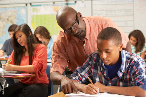 Wallpaper Mural Teacher Helping Male Pupil Studying At Desk In Classroom