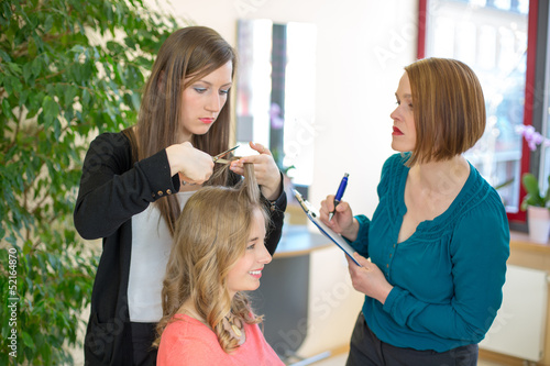 Apprentice cutting hair while instructor is watching