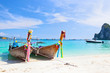 Tropical island with two boats and a bright sky