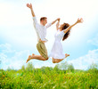 Happy Couple Outdoor. Jumping Family on Green Field