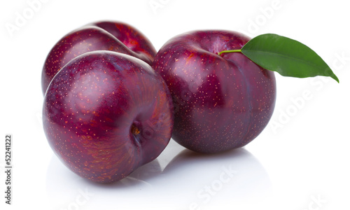 Photo Three ripe purple plum fruits with green leaves isolated