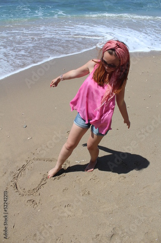 Photo Beautiful rehead young woman drawing heart in the sand