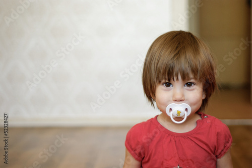 Fotografie, Obraz  girl with a soother in her mouth