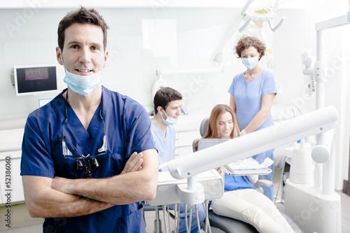 obraz PCV Portret dentysta z jego zespół pracuje w tle