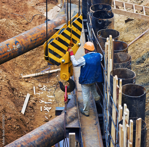 Photo  construction worker directs a lifting mechanism