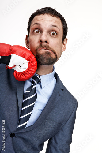 Vászonkép Young business man struck by hand in boxing glove