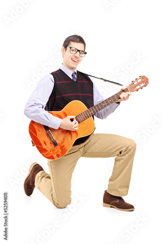 Keuken foto achterwand Art Studio Young man playing an acoustic guitar and kneeling