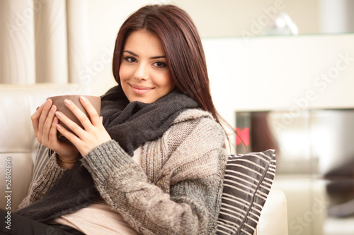 Fotografie, Obraz  Happy young woman sitting on sofa in cosy cloths
