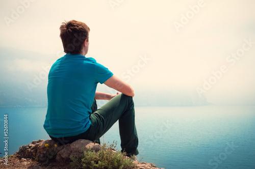 Fotografía  Lonely guy looking into the distance at sea