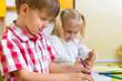 Two cute little prescool kids drawing