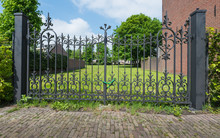 Ornate Wrought Iron Gate With A Chain And Padlock.