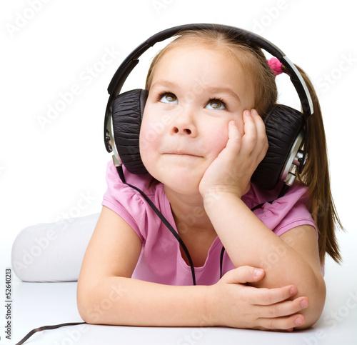 Fotografia  Cute little girl enjoying music using headphones