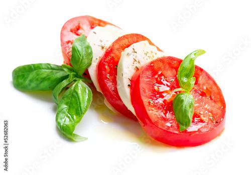 Fotografie, Obraz  Caprese Salad. Tomato and Mozzarella slices with basil leaves