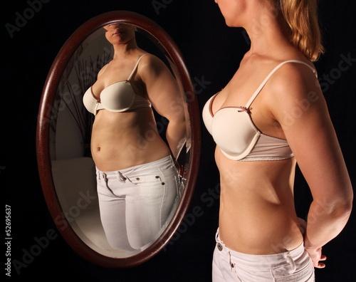 Fotografía  Schlanke Frau sieht sich dick im Spielgel