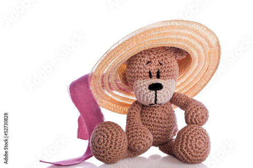 brown teddy bear with sun hat and pink ribbon