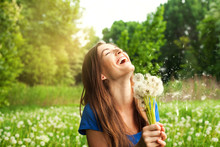 Portrait Of Laughing Girl With Dandelions At The Park