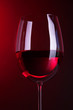 Glass of wine on bright red background