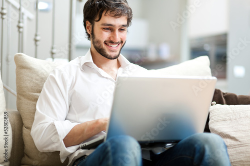 Fotografia  Young man relaxing on the sofa with a laptop