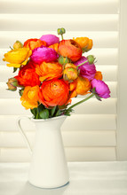 Flowers In A Vase With Sun Light Coming Out Of Window Blinds