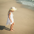 happy little girl standing on beach