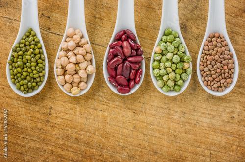 Verschiedene Hülsenfrüchte auf Porzellanlöffeln