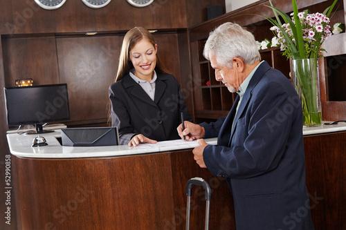 Fotografie, Obraz  Gast unterschreibt Formular im Hotel