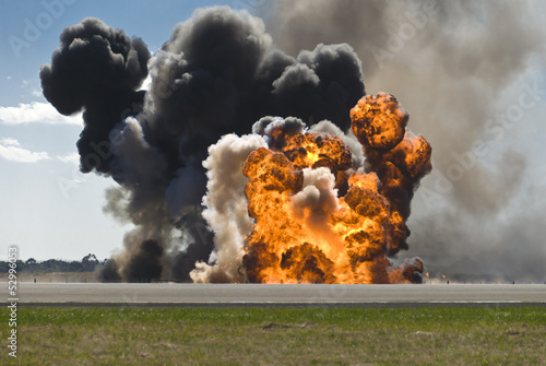 Photo Fiery explosion with thick black smoke on an airport runway.